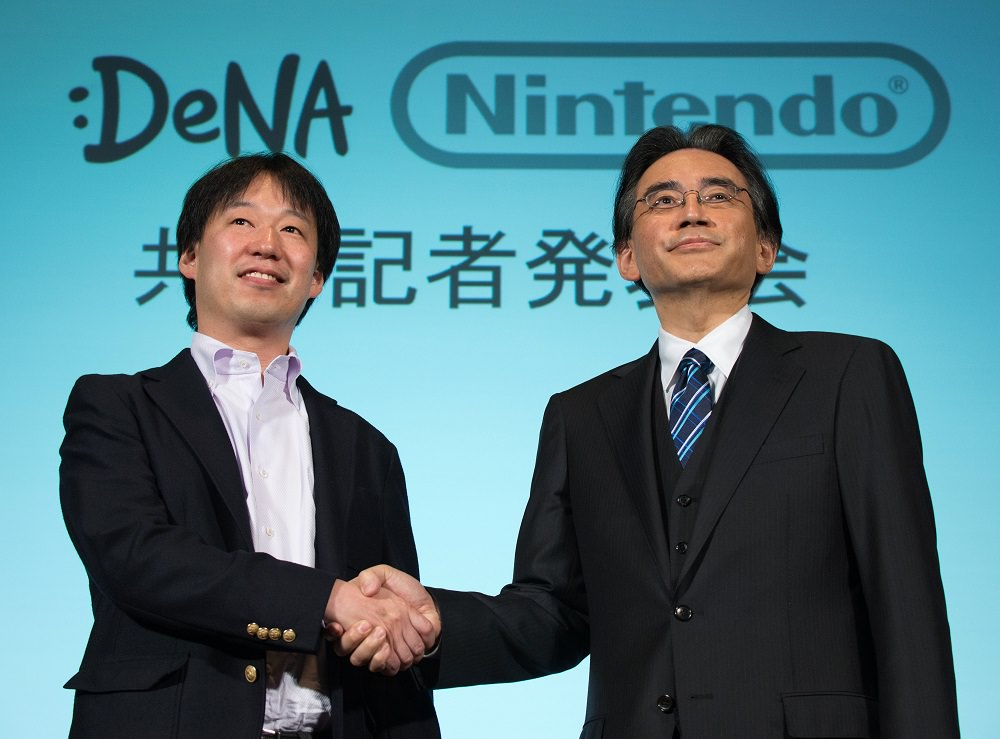 Satoru Iwata, president of Nintendo Co., right, and Isao Moriyasu, president and chief executive officer of DeNA Co., shake hands during a joint news conference in Tokyo, Japan, on Tuesday, March 17, 2015. Nintendo dropped its resistance to using its characters on mobile devices as the maker of Mario and Zelda teams with DeNA to develop new games for smartphones and tablet computers. Photographer: Akio Kon/Bloomberg *** Local Caption *** Satoru Iwata; Isao Moriyasu