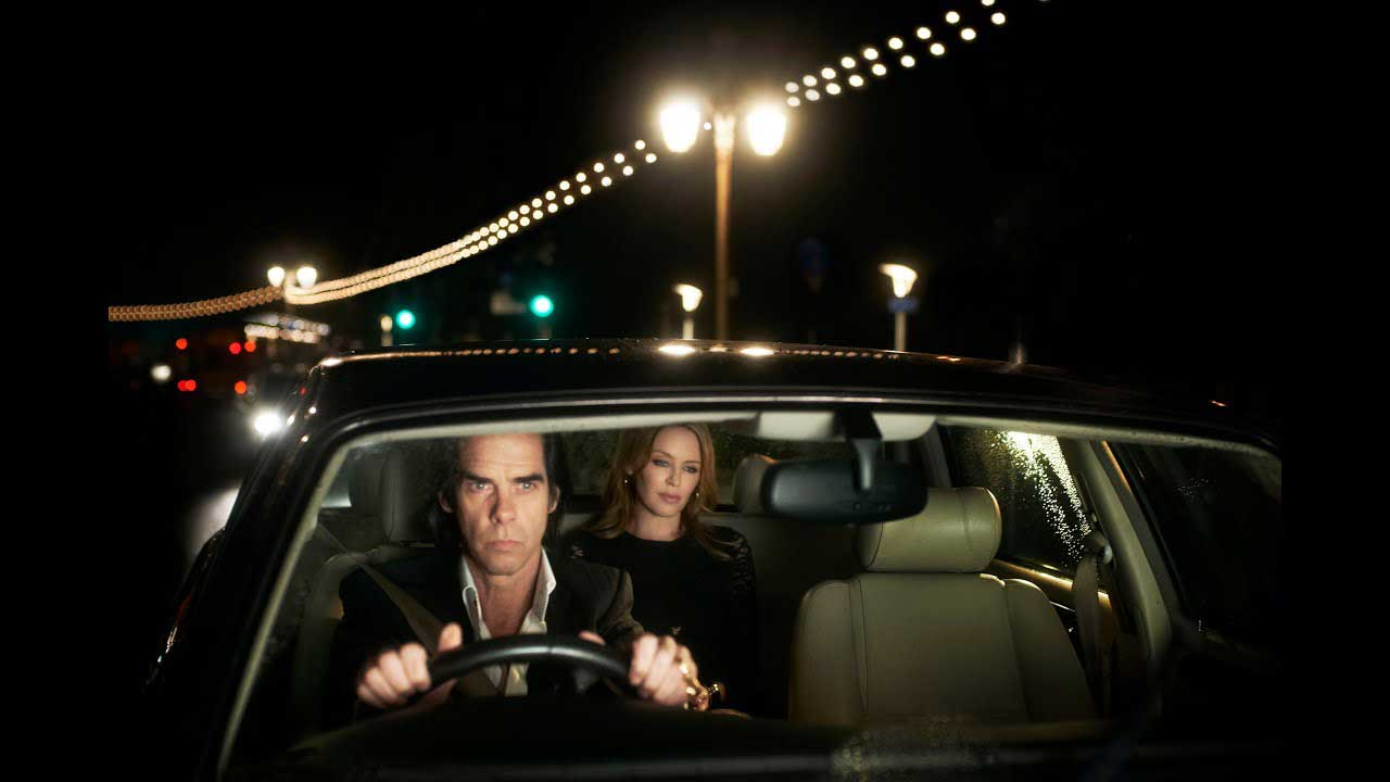 A serious man driving on the bright streets of the city in the movie 20,000 Days on Earth