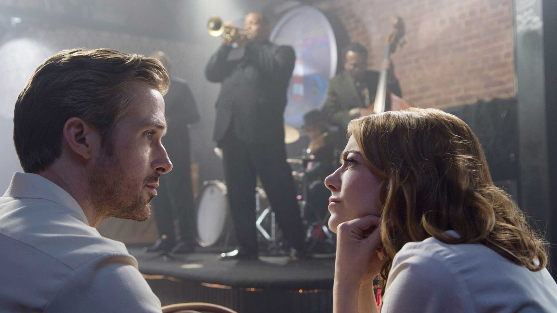 Ryan Gosling and Emma Stone look at each other in front of musician Damien Chassell in La La Land
